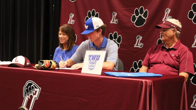 Lakeside first baseman Kohl Chambers signs a scholarship with Tennessee Wesleyan University on Friday in the Lakeside auditorium. Chambers is expected to play first base and pitch for the Bulldogs.