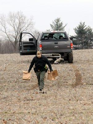 Fairfield County Sheriff's Deputy Chris Walker walks away from a pick-up truck in field Tuesday, Jan. 23, 2018, in the 2200 block of Carroll Southern Road in Greenfield Township.