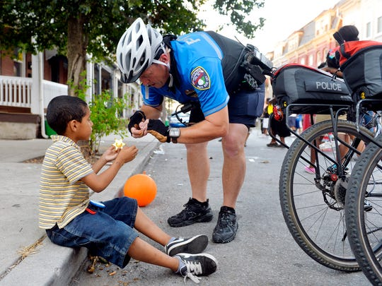 York City Police lieutenant Erik Kleynen, right, attaches a pin to a toy deputy badge given to him by Juan Andrew Martinez, 6, during National Night Out on Tuesday, Aug. 4, 2015, in the 200 block of East College Street in York City.