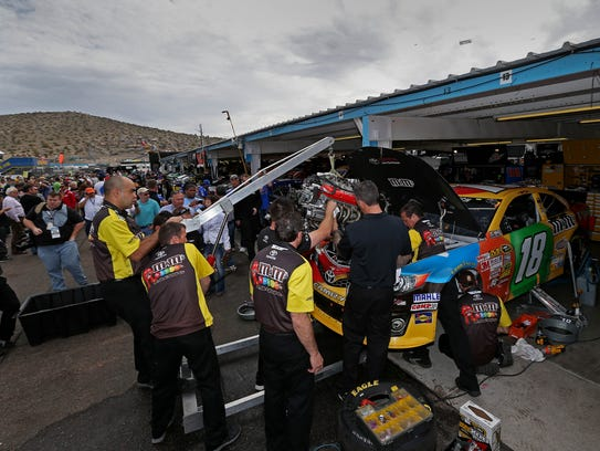 Crew members change engines in the car of Kyle Busch