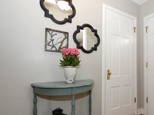 With a grouping of mirrors and an accent table, the