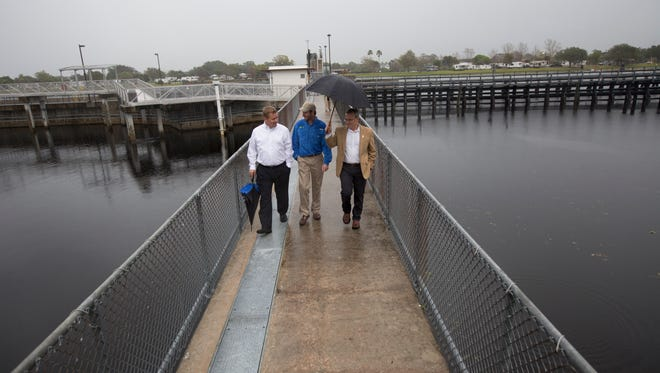 Eric Eikenberg, Director of the Everglades Foundation, center, is flanked by realtor, Shane Spring, left, and Steve Davis, an ecologist for the Everglades Foundation stroll the Franklin Locks on Tuesday.  They were holding a press conference on the quality of water that is being released down the Caloosahatchee River.