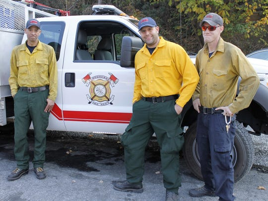 In this Nov. 16, 2016 photo, Edward Nieto, Ryan Baca and Christian Mee, firefighters from Albuquerque, N.M., drove 23 hours to help fight the wildfires near Lake Lure, N.C.2016. Firefighters from across the country have come to western North Carolina to help fight the fires.