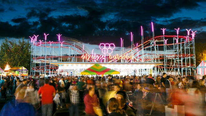 Crowds mill around the Oregon State Fair as the fair's first roller coaster since 1967 runs on Sept. 4, 2016. The ride, called the Olympic Bobsled, took a crane and nearly a week to assemble. It is 70 feet tall and features several twists and turns along a quarter mile track.
