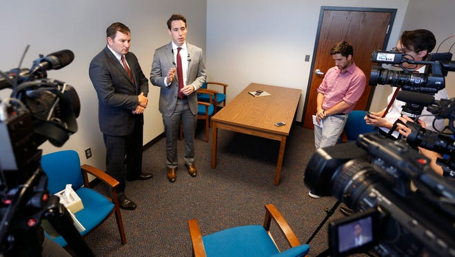 Missouri Attorney General Josh Hawley (center right) and Greene County Prosecuting Attorney Dan Patterson talk about seeking a restraining order against massage parlors after investigators raided 13 businesses and five houses Thursday in connection with an investigation into what authorities believe could be a sex trafficking ring connected to organized crime.