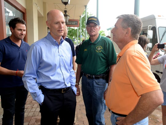 Then-Gov. Rick Scott chats with former Pensacola News Journal Publisher Terry Horne, right, during Scott's tour of flood damage in Pensacola in April of 2014.