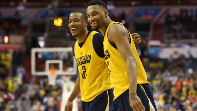Michigan guards Zak Irvin , right, shares a laugh with teammate Muhammad-Ali Abdur-Rahkman after defeating Illinois during the Big Ten conference tournament at Verizon Center.