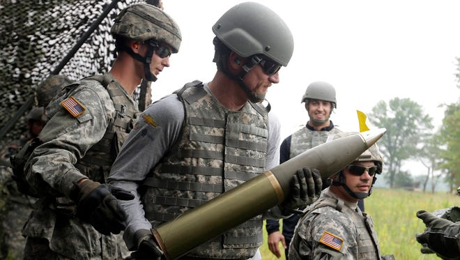 Dale Earnhardt Jr. prepares to load a shell into a M119 Howitzer at Camp Atterbury in Edinburgh, Ind., during a visit Wednesday.