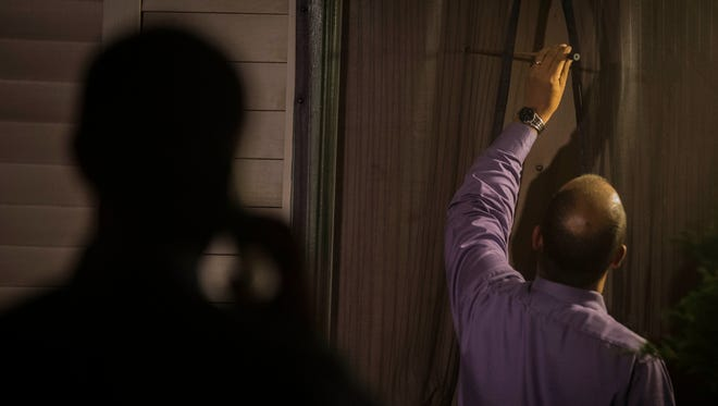 Burlington police investigators measure a bullet hole in the front door of an apartment off Hyde Street Wednesday night after someone fired several shots from the street into the building. No one was hurt in the incident, but one bullet entered into an apartment with small children inside.