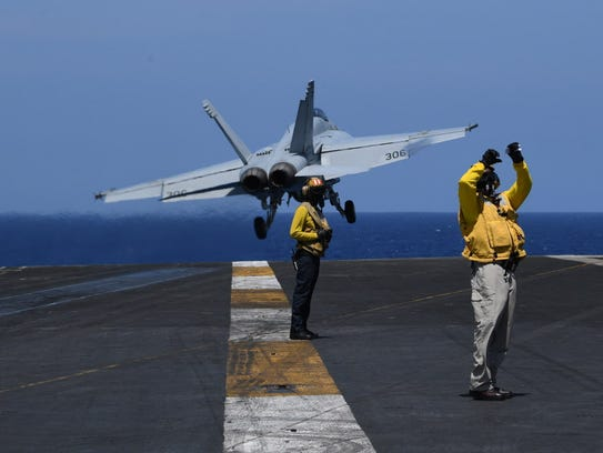 U.S. sailors stand on the flight deck while an FA-18