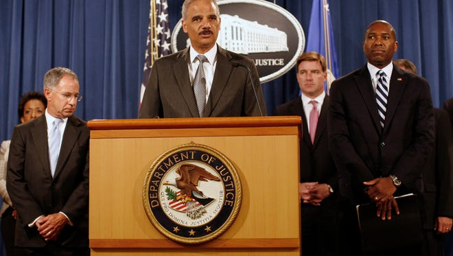 U.S. Attorney General Eric Holder, center, announces a settlement with Bank of America at the Justice Department in Washington.