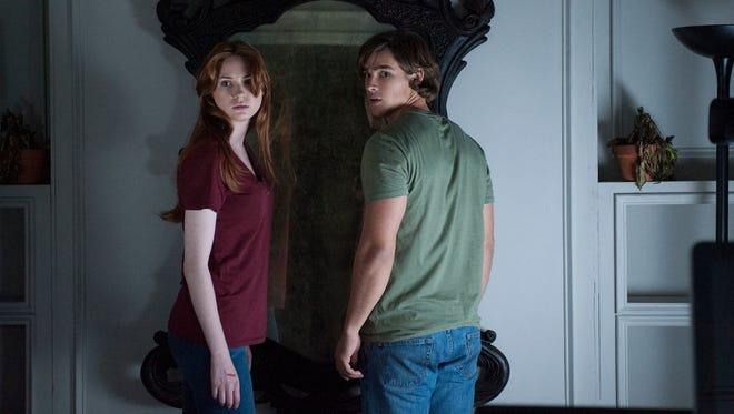 "Karen Gillian and Brenton Thwaites grapple with a malevolent mirror in the new horror thriller ""Oculus."""