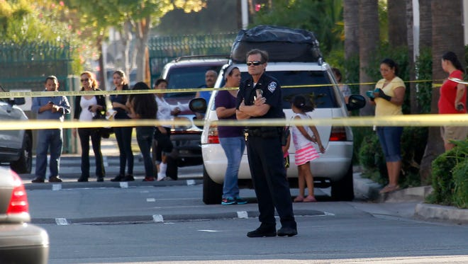 A police officer stands by the scene of a shooting in Bell Gardens, Calif., Tuesday.