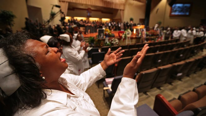 A woman raises her hands during the funeral of Michael Brown inside Friendly Temple Missionary Baptist Church on Aug. 25 in St. Louis.