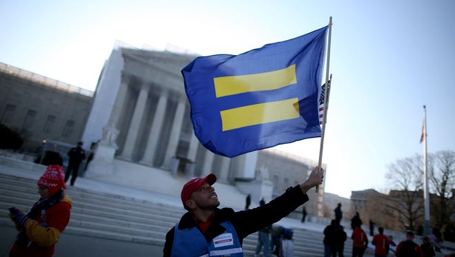 Marcos Garcia holds an equality flag in front of the U.S. Supreme Court before the court hears arguments about gay marriage on March 27.
