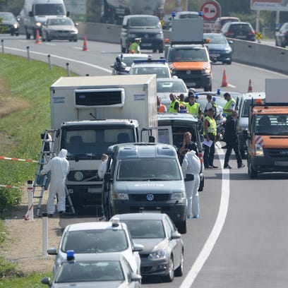Forensic officers stand in front of a truck found in eastern Austria Aug. 27, 2015, that contained the bodies of at least 20 refugees.