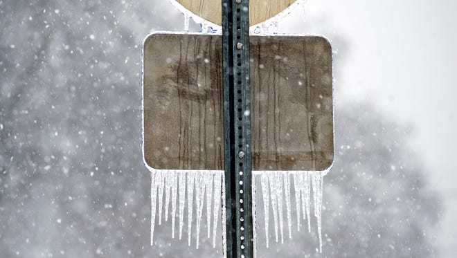 The back of a road sign is coated with trails of ice as snow falls, Friday morning Jan, 22, 2016, in Bowling Green, Ky. (Miranda Pederson/Daily News via AP) MANDATORY CREDIT