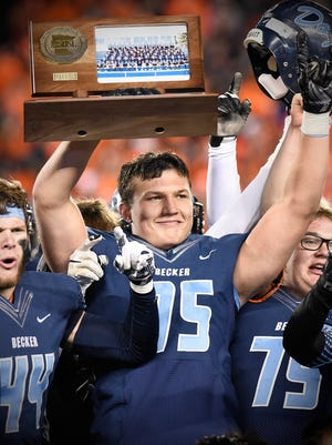 Becker's Dillon Radunz holds the trophy as players celebrate their state title after beating South St. Paul in the Nov. 13 Class 4A state title game at TCF Bank Stadium in Minneapolis.