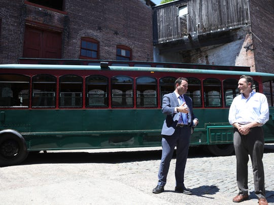 Mayor Andre Sayegh and David Garsia, of the Art Factory, are shown during a press conference introducing a trolley service for Paterson. That service is unlikely to be available until mid- to late October at the earliest.