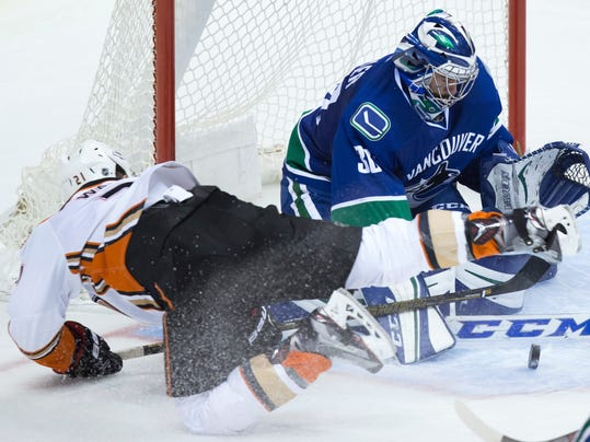 Anaheim Ducks' Chris Wagner, left, is stopped by Vancouver Canucks goalie Ryan Miller as he falls to the ice during the second period of an NHL hockey game Thursday, Dec. 1, 2016, in Vancouver, British Columba. (Darryl Dyck/The Canadian Press via AP)