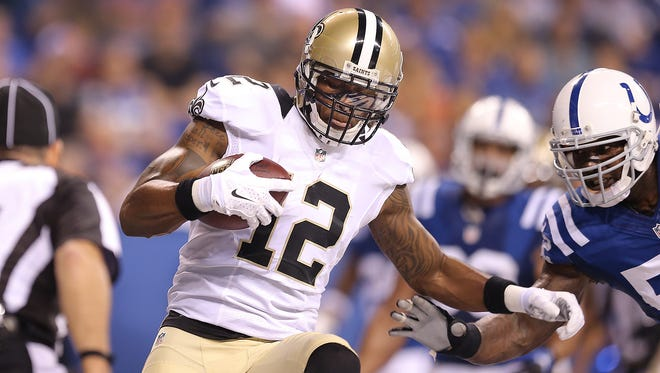New Orleans Saints Marques Colston,#12, makes a touchdown catch behind Indianapolis Colts DÕQwell Jackson,right, in the first half of their game. The Colts hosted the Saints in preseason football game Saturday, August 23, 2014, evening at Lucas Oil Stadium.