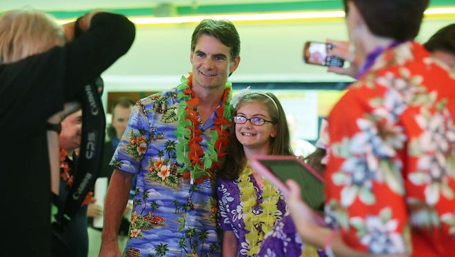 Olivia Pierce, 8, Hobart, a cancer survivor treated at Riley, poses with Jeff Gordon as a photographer and Olivia's mom Shannon Pierce, right, take a photo. The 13th Annual Bowling Tournament benefiting The Jeff Gordon Children's Foundation Pediatric Cancer Research Fund at Riley Hospital for Children was held at Western Bowl Thursday July 24, 2014.