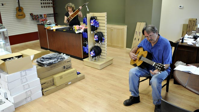 Hams Music owner Al Hams tunes a guitar as his wife, Teri, unpacks another in 2009 at his new music store in St. Cloud. Hams is retiring and closing his store next month because of health issues.