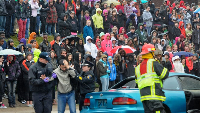 Technical High School students watch as an accident scene is simulated near the school Thursday. The mock crashes are held at high schools throughout the area to show students the dangers of drinking and driving.