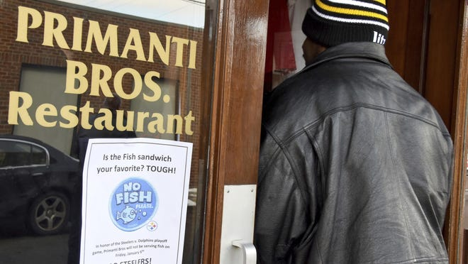 """A sign posted on the door of Primanti Bros. Restaurant says """"Is the Fish Sandwich Your Favorite? TOUGH"""", Friday, Jan. 6, 2017 in Pittsburgh. Primanti Bros. Restaurant won't serve fish leading up to Sunday's NFL playoff game between the Steelers and the Miami Dolphins. (Darrell Sapp/Pittsburgh Post-Gazette via AP)"""