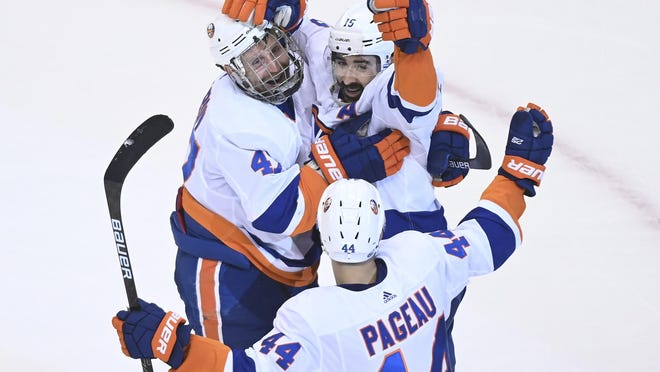New York Islanders right wing Cal Clutterbuck (15) celebrates his goal with teammates Leo Komarov (47) and Jean-Gabriel Pageau (44) while playing against the Washington Capitals during third-period NHL Eastern Conference Stanley Cup playoff hockey action in Toronto, Friday.