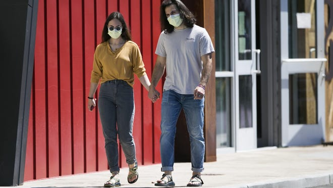 Hana Morris, left, and Forrest Golic wear masks as they walk hand in hand Monday in Yakima, Wash.