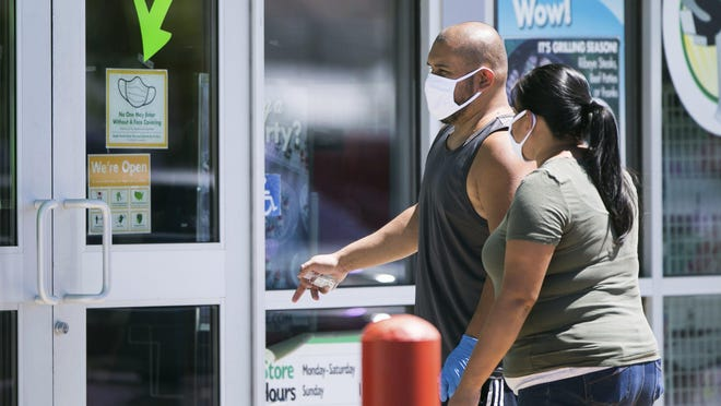 A mandatory face protection sign hangs on a window of the Dollar Tree as T.J. George, left, and Roberta George walk toward the front entrance Monday, June 22, in Yakima, Wash.