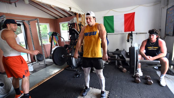 Worcester State senior linebacker Gus Ramstrom works the weights, while working out with former Syracuse University running back Otto Zaccardo (left) and Merrimack College senior defensive lineman Troy Shallow at Shallow's home gym in Sudbury, July 24, 2020.