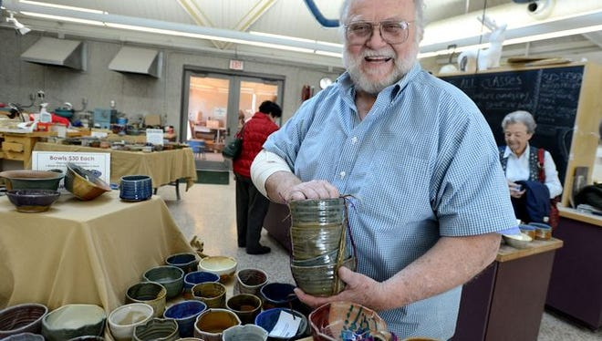 """Bill Clover, a Pensacola State College visual arts professor,  shows off some of the bowls that will be available during the ninth annual """"Pick a Bowl"""" for MANNA fundraiser set for Nov. 13."""