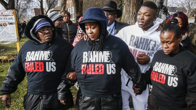 Janet Cooksey, center, the mother of 19-year-old Quintonio LeGrier, is supported by relatives and neighbors as she walks from the location where Chicago police shot her son.
