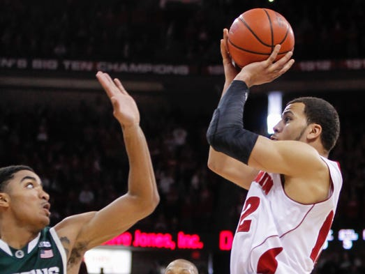 Wisconsin's Traevon Jackson shoots the game-winning basket against Michigan State's Gary Harris (14) and Adreian Payne during the final seconds of Wisconsin's 60-58 upset of No. 8 Michigan State.