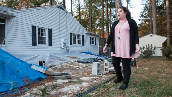 Samantha Keyes, stands alongside her home which was recently damaged by heavy storms on Wednesday, Nov. 16, 2016.