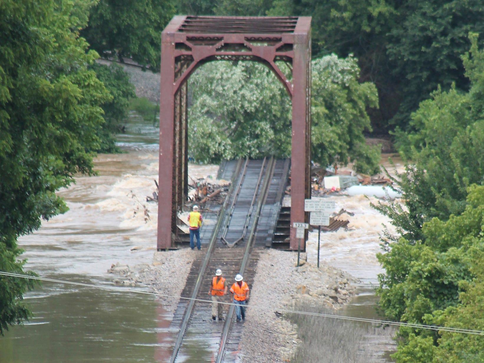 Burlington Northern Santa Fe Railroad crews inspect the tracks as water from the Gasconade River and Little Piney Creek rise under a bridge near Arlington, Mo.