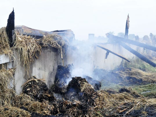 Rubble is all that remains after a Fire completely destroyed a barn at 7735 Edenville-Cheesetown Road, St. Thomas Township Wednesday, June 3, 2015. The fire was reported at aSt. Thomas area barn fire. round 8:30 p.m. and firefighters saw flames billowing from a hay barn when they arrived.
