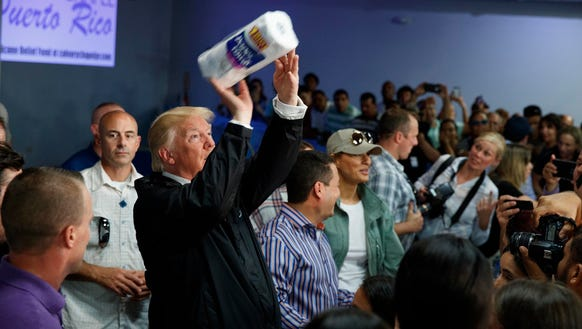 President Donald Trump tosses paper towels into a crowd