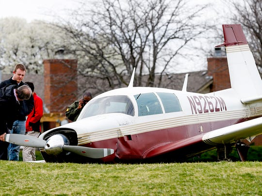 Authorities check out a small plane that crashed on the 14th hole at the Tallgrass Country Club in Wichita, Kansas, on Friday.
