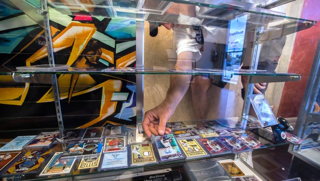 Steve Palmer, owner of BreakRoom Sports Cards & Autographs sorts through some of his collectible baseball cards at his new shop located on Southeast 47th Terrace in Cape Coral.