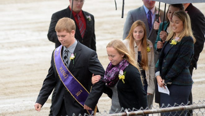 Joe Batchelor, 2014 Coshocton County Fair King, escorts queen candidate Amy Jo Johnson on stage during the king and queen crowning ceremony Saturday in Coshocton.