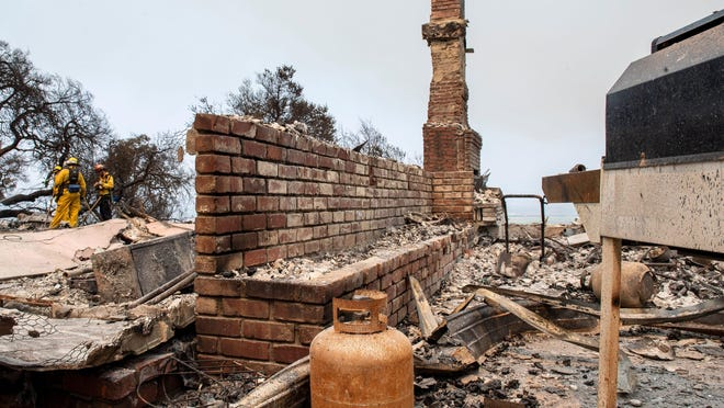 Firefighters survey damage and clean up debris on Aug. 18 in Salinas, Calif. Recent wildfires have ravaged the region.