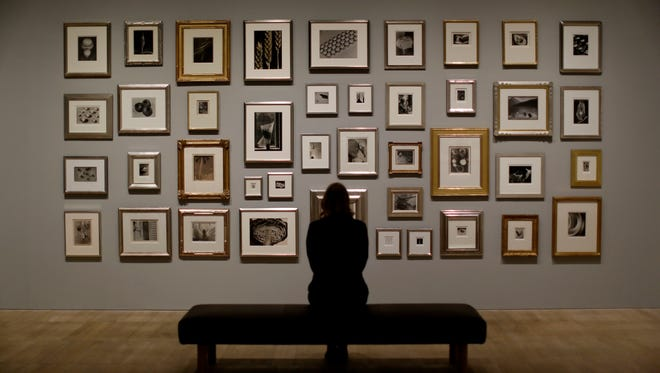 "A Tate member of staff poses in front of a wall of photographs at the press view of ""The Radical Eye: Modernist Photography from the Sir Elton John Collection"" exhibition at the Tate Modern gallery in London, Tuesday, Nov. 8, 2016. British musician Elton John's collection of international modernist photography from the 1920s to 50s includes almost 200 prints and opens to the public on November 10. (AP Photo/Matt Dunham)"