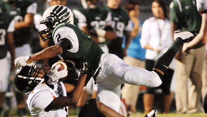 Hug running back Jalan Williams is pulled down by Ivan Romero of Fernley in their season-opening game on Aug. 29.