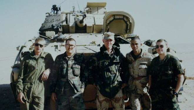 Servicemen stand in front of a Bradley fighting vehicle in Saudi Arabia before entering Iraq in the first Gulf War in 1991.  -Photographer's caption:-  -Text: ** ADVANCE FOR SUNDAY, JUNE 8 **Sgt. Russell Holloway, center, poses with his crew in front of their Bradley fighting vehicle in Saudi Arabia prior to entering Iraq in the first Gulf War in 1991. On the right is 1st Lt. John Hillen, the ranking officer. Others were not identified. The snapshot was from Holloway's personal collection. (AP Photo/Peter Cosgrove)