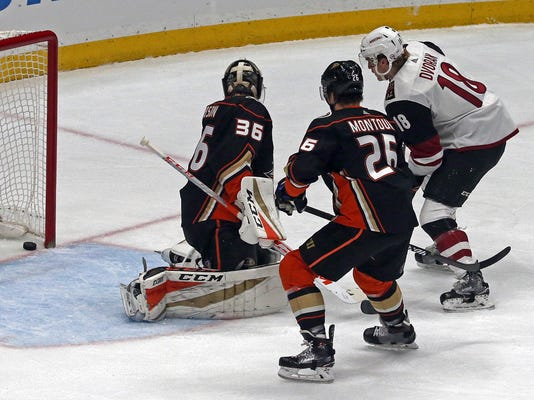 Anaheim Ducks goalie John Gibson (36), Ducks defenseman Josh Manson (42) and Arizona Coyotes center Christian Dvorak (18) watch a goal by left winger Brendan Perlini in the first period of an NHL hockey game in Anaheim, Calif., Sunday, Dec. 31, 2017. (AP Photo/Reed Saxon)