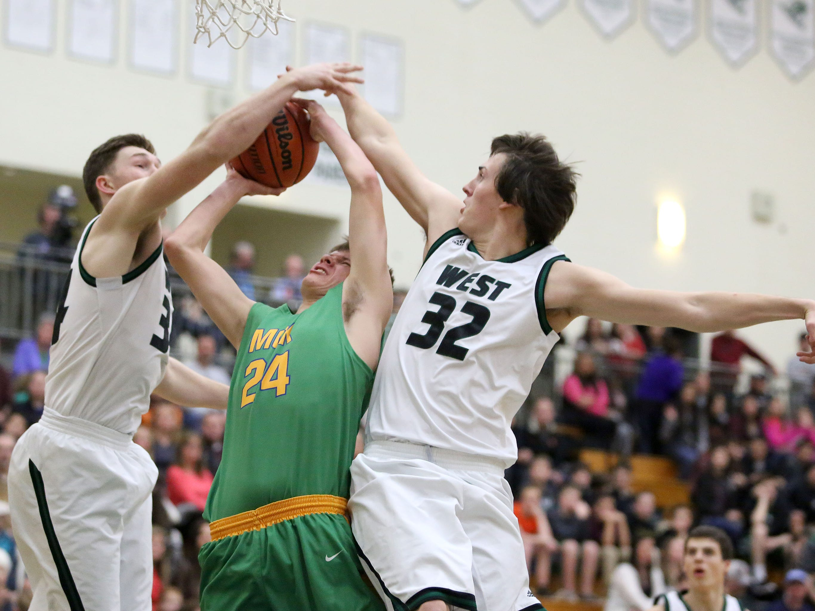McKay's Tristen Wilson (24) has his shot blocked by West Salem's Jacob Kizer and Nate Hall (32) during their Greater Valley Conference game on Friday.