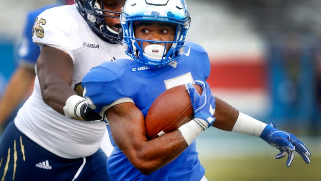 MTSU's Jocquez Bruce (5) runs the ball as FIU's Josh Little (96) moves in for the tackle during the game Saturday, Oct. 7, 2017.